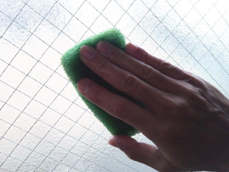 濡らしたスポンジを使って窓拭き