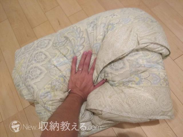 羽毛布団を押して空気を出す